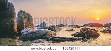 Tropical colourful sunset on the beach, Koh Chang island, Thailand. Panorama view of dark night sea with protruding stones