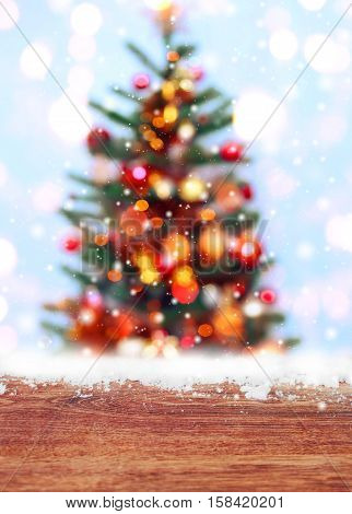 Wooden table with snow place and Christmas tree background with blurred sparking glowing. Happy New Year and Xmas theme