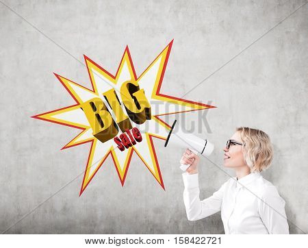 Woman With A Megaphone Near A Big Sale Poster On A Concrete Wall