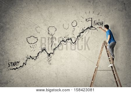 Creative moment: a young man drawing on the wall