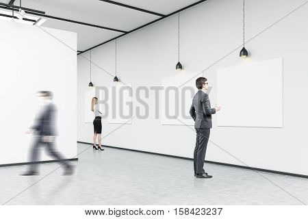 Side view of a man with a paper cup of coffee looking at a picture on white wall. His colleague is passing by. Blond girl in background. Concept of cultural event. 3d rendering. Mock up.