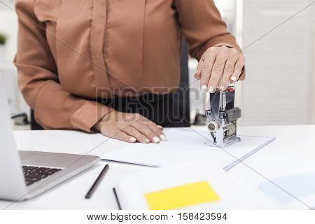 Woman in brown blouse using a stamp on a document. She is sitting in a white office with her laptop on the desk