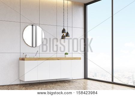 Corner of a bathroom interior with a tiled wall a round mirror and a long sink counter. 3d rendering.