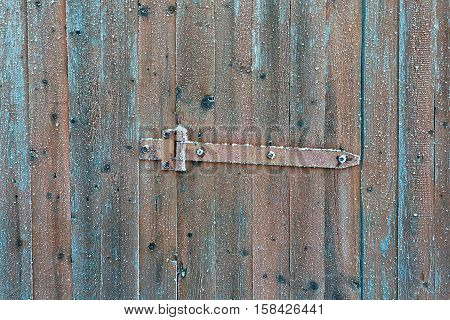 Rusty locking slide latch on frozen wooden old door in the winter with snow flakes on it as a rustic background.