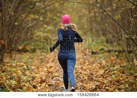 Young sportswoman in autumn forest
