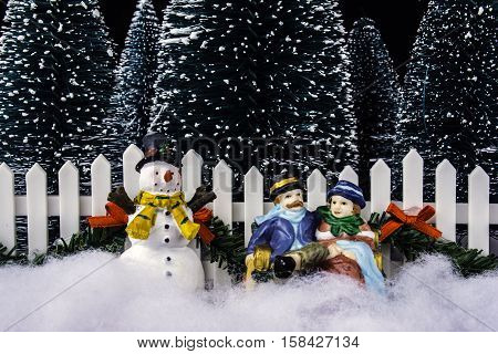 miniature Christmas scene of couple sitting on park bench in snow with snowman pine trees and white picket fence