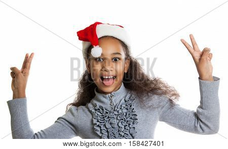 Cheerful Dark-skinned Girl In A Red Scarf And Hat Of Santa Claus. Winter Portrait Of Joyful Adolesce