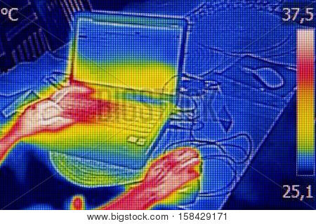 Infrared thermography image showing the heat emission when woman used notebook