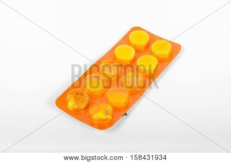 Pack of yellow pills on withe background