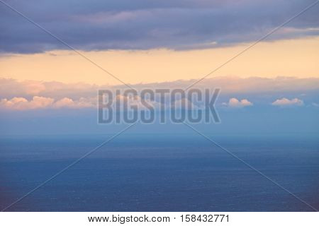 Marine horizontal landscape at sunset. The sea or ocean is clean, with no facilities. The sea becomes the sky. Horizon blurred. In her pink cloud of solar light. Beautiful sunset. Calm sea. Gloomy sky with gleams of sunshine. The sky and clouds.