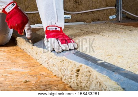 Man is measuring rock wool for attic insulation