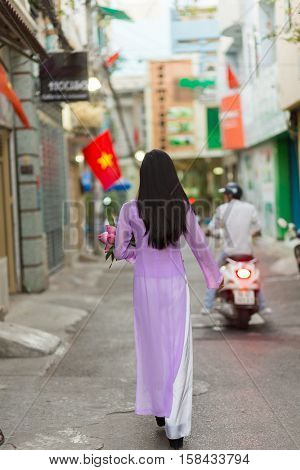 Vietnamese woman walking in Ho Chi Minh street wearing Ao Dai traditional dress, carrying lotus flowers with the Vietnam flag in background .