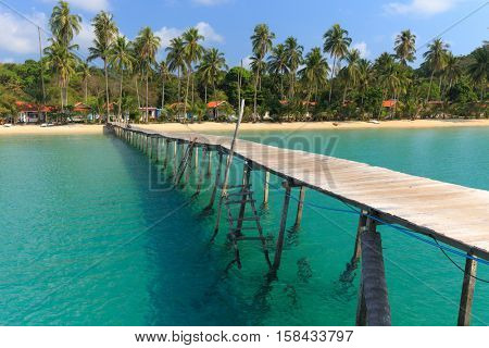 Wooden pontoon in the turquoise tropical sea of Ao Phrao beach in Koh Kood island, Thailand .