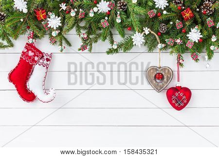 Christmas Background. Christmas Fir Tree Branches, Christmas Socks On White Wooden Board Background.