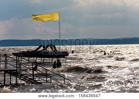 Lake Balaton beach in backlight with silhouettes of bathers and paddle boats