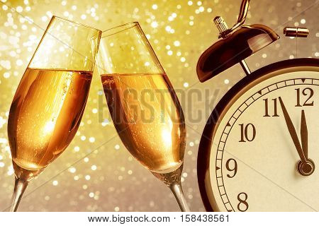 Champagne Flutes With Golden Bubbles On Golden Light Bokeh Background With Vintage Alarm Clock