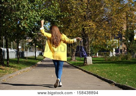 Beautiful woman in yellow coat walking autumn street