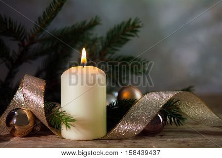 white burning candle with christmas or new year decoration spruce twigs baubles and a golden ribbon on rustic wood copy space selective focus and narrow depth of field