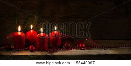 Four red burning candles for the fourth advent christmas decoration with spruce twigs and baubles on a rustic board dark wooden background with copy space panorama banner or website header selective focus