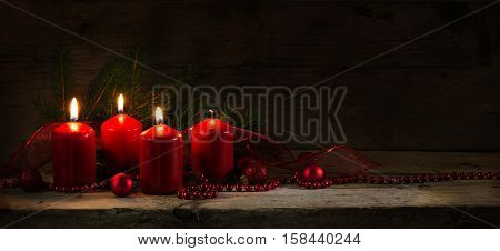 Four red candles three of them burning on the third advent christmas decoration with spruce twigs and baubles on a rustic board dark wooden background with copy space panorama banner or website header selective focus