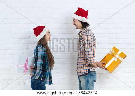 Christmas Holiday Happy Couple Hold Surprise Present Boxes Wear New Year Santa Hat Cap, Man And Woman Smiling Over White Brick Wall