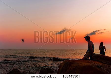 man and woman watching the sunset on the sea.
