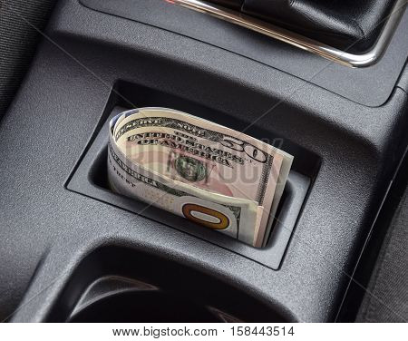 Several Banknotes American Dollars Lie In The Niche Of The Central Console Of The Car. The Money In