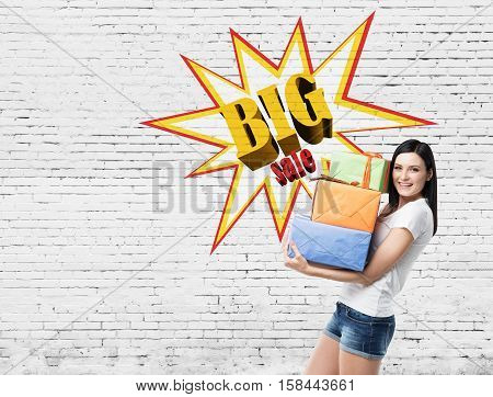 Smiling woman wearing shorts and a T-shirt and holding presents near a brick wall with a big sale poster on it. Mock up