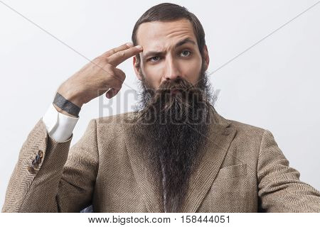 Close up of businessman with long beard wearing a beige suit and sitting against white background.