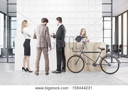 Peopple are talking in an office with white tiles on the wall behind a reception counter. A bicycleis standing near it. A conference room in the background. 3d rendering. Mock up