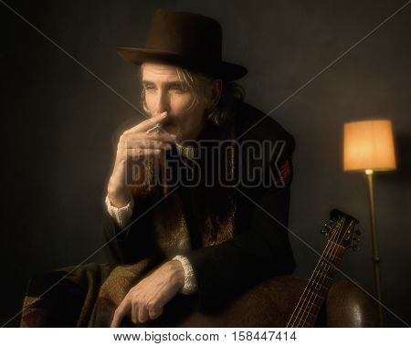 Vintage 1970S Guitarist Leaning On Back Of Chair And Smoking Cigarette.