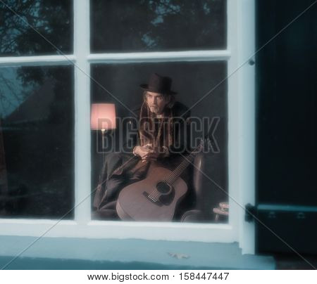 Vintage 1970S Guitarist Leaning On Back Of Chair Behind Window.