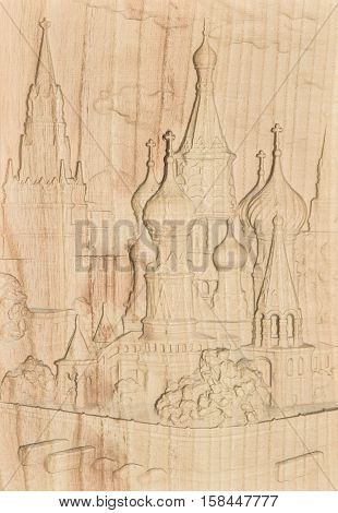 Woodcarving. Carved relief image of the Moscow Kremlin on a wooden plank.