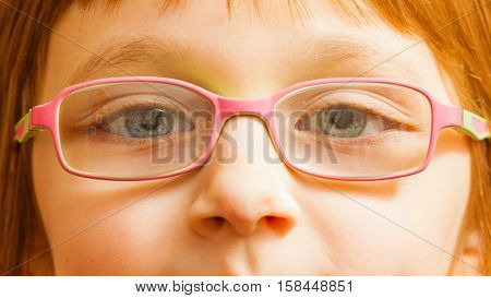 Eyeglasses vision eye problems concept. Closeup face of young toddler girl wearing pink glasses for kids.