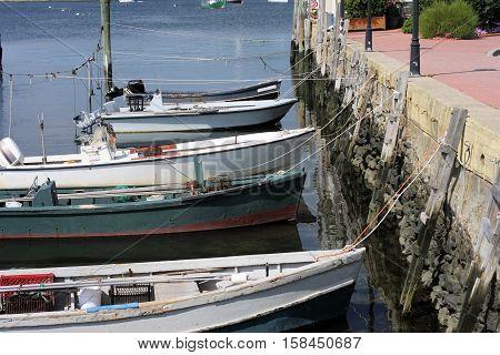 Five work skiffs tied to a concrete dock.
