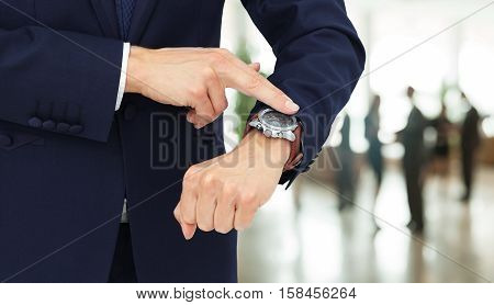 on the left side of the photo close-up of businessman with finger point at his watch in his hand. on the right side of the photo on the background of the office there's an empty space for your text
