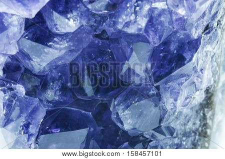 Purple amethyst stone isolated on white (rough amethyst crystals)
