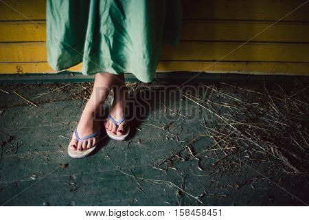 View of female feet in opened slippers with painted nails and greenish dress yellow wooden wall on the background dry grass or hay around