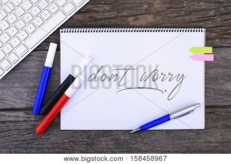 Notebook with dont worry Handwritten on wooden background and Modern Computer Keyboard. Top View Composition