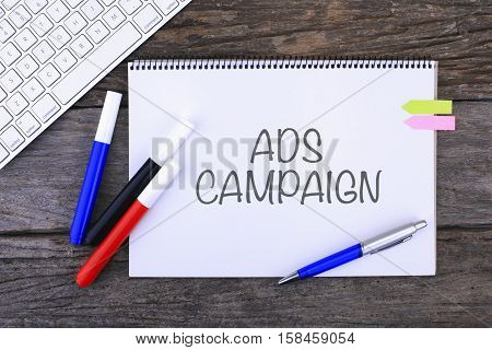 Notebook with ADS CAMPAIGN Handwritten on wooden background and Modern Computer Keyboard. Top View Composition