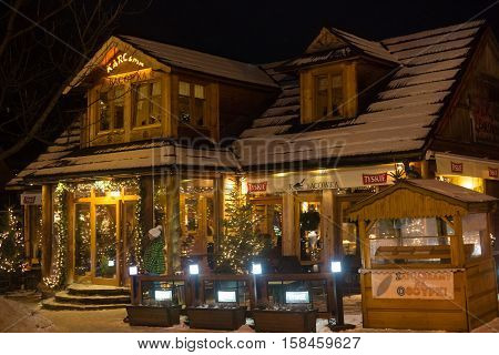 POLAND ZAKOPANE - JANUARY 03 2015: Traditional wooden restaurant on the street in Zakopane in the Christmas decoration. Town known as the winter capital of Poland. It is a popular destination for tourism.