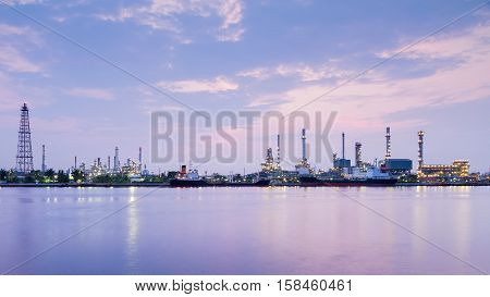 Panorama over oil refinery river front with sunrise sky background