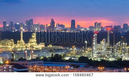 Petroleum manufactory refinery with city downtown background