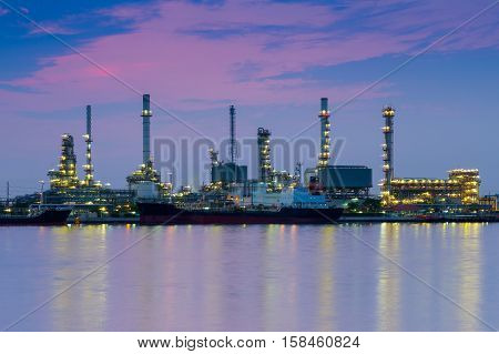 Oil refinery river front with twilight sky background after sunset