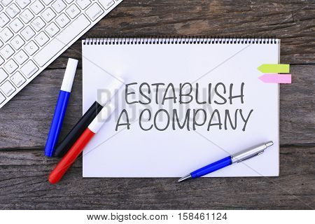 Notebook With Establish A Company Handwritten On Wooden Background And Modern Computer Keyboard. Top