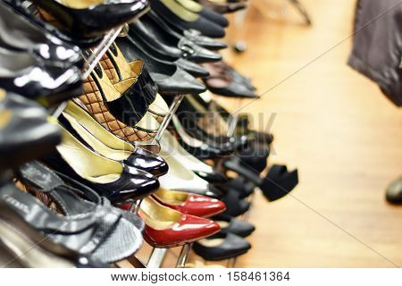 Rows of stylish women's shoes and high heels on a rack for sale at a clothing store