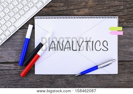 Notebook with ANALYTICS Handwritten on wooden background and Modern Computer Keyboard. Top View Composition