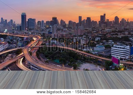 Opening wooden floor, City business downtown with highway intersection and dramatic sunset sky background