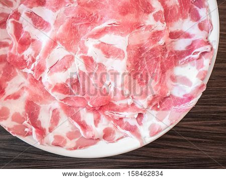 Plate of sliced meat on wooden tabletop