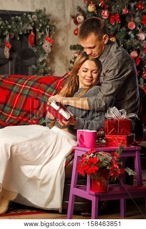 Loving couple and Christmas. Girl hugging boyfriend. She is holding a Christmas gift. In the background a beautiful Christmas tree. Bear hug.
